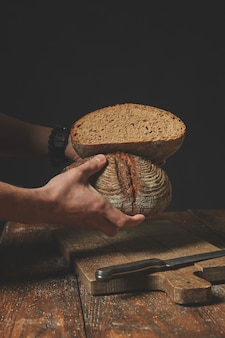Mannenhanden houden twee helften roggebrood vast op een donkere achtergrond