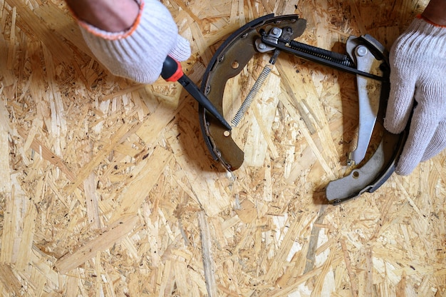 Mannenhanden in gehandschoende zijn ruimen en gerepareerd met een lange tang autotrommelrem gedemonteerd op een vel osb triplex achtergrond. plat lag, bovenaanzicht