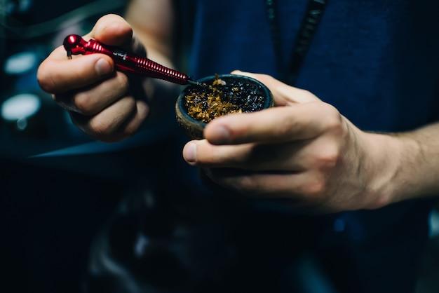 Mannenhanden mengen verschillende tabak voor shisha in de kom