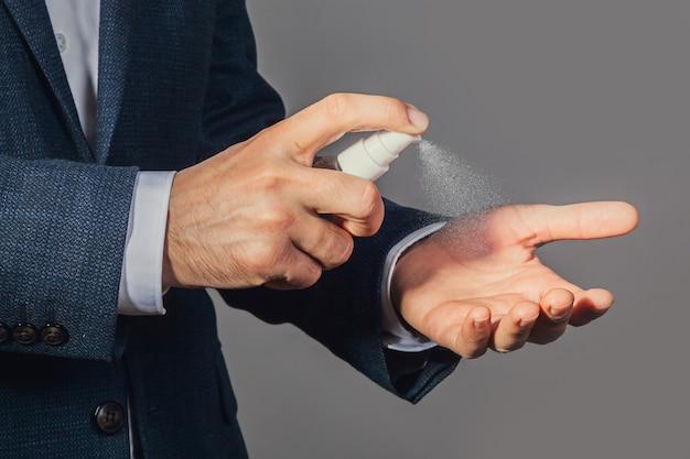 Mannenhanden met behulp van antibacteriële antiseptische spray