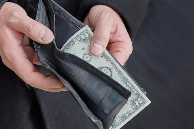 Mannenhanden met een gescheurde portefeuilleclose-up. concept van armoede en werkloosheid