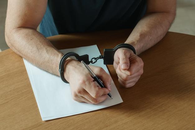 Mannenhanden met handboeien vullen het politieverslag, bekentenis. bovenop het politieonderzoek