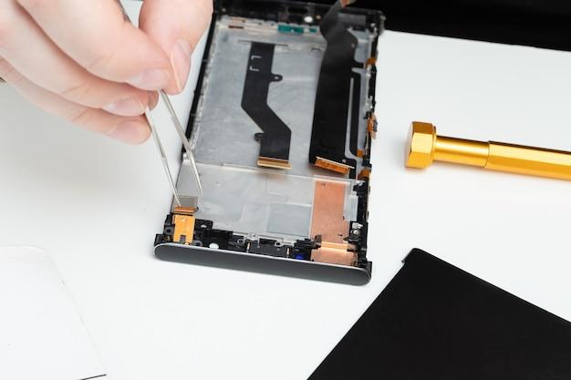 Mannenhanden repareren een mobiele telefoon, installeren reserveonderdelen met speciaal gereedschap