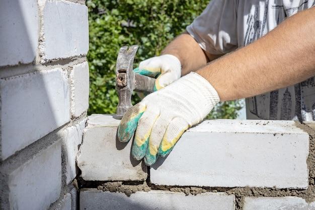 Mannenhanden repareren het metselwerk met een hamer