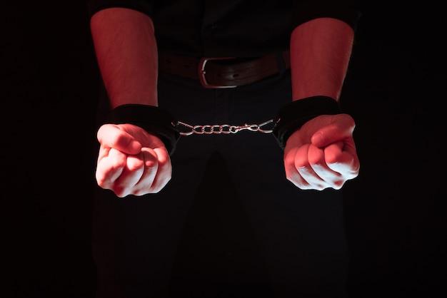 Mannenhanden vastgeketend in lederen handboeien voor bdsm-seks achter zijn rug. onderwerping en overheersing