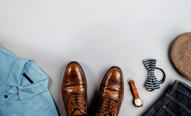 Mannenkleding, vaderdagconcept. vintage-stijl. plat lag op lichtgrijze achtergrond. inclusief vleugeltips kleding schoenen, hand horloge, vlinderdas, hoed, shirt, jeans en zonnebril. stijlvolle mannen. bovenaanzicht