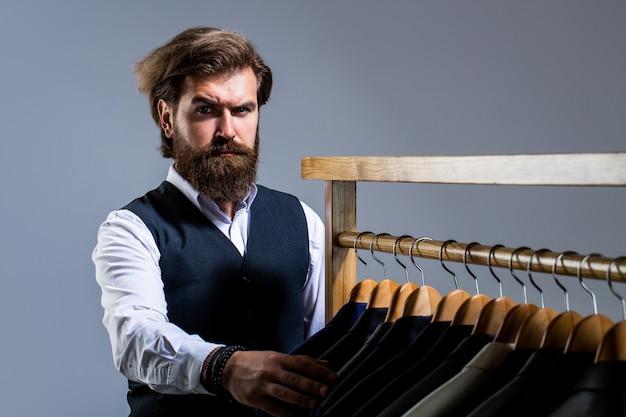 Mannenkostuum, kleermaker in zijn atelier. mannelijke pakken die in een rij hangen. op maat, maatwerk. stijlvol herenpak. knappe bebaarde mode man in klassiek kostuum pak.