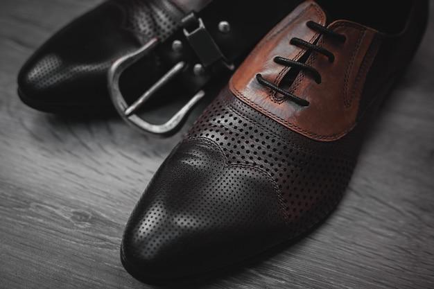 Mannenmode met schoenen met riem op houten
