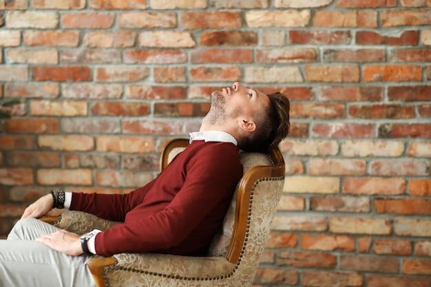 Mannenmode op houten vloer, jonge man die zich voordeed