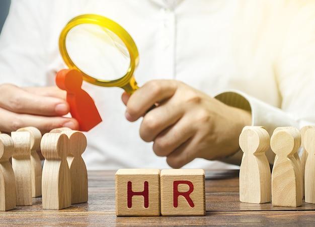 Mannenwerkgever die een potentiële werknemerskandidaat met vergrootglas onderzoekt