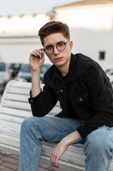 Mannequin coole jonge man in stijlvolle jeans kleding rechtzetten trendy bril. amerikaanse stijlvolle man in casual denimkleding met zwarte leren rugzak poses op bankje op straat. jeugd outfit herenkleding.