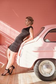 Mannequin die op roze auto leunt. jonge vrouw die ernaar uitkijkt. vintage-stijl.