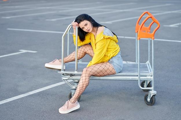 Mannequin gekleed in moderne gele jas, jeugd panty, denim shorts en stijlvolle roze sneakers poseren op winkelwagen