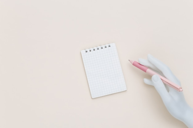 Mannequin hand houdt pen en notitieblok op beige achtergrond. bovenaanzicht