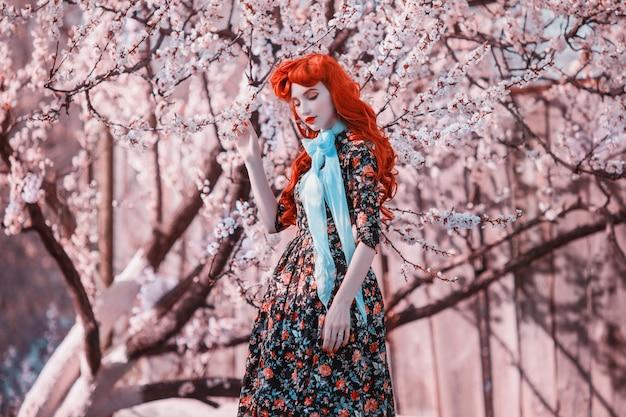 Mannequin in de lentebloem tuin. valentine dag achtergrond. retro jurk. fantastische roodharige dame in jurk. vrouw in blauw lint op aard achtergrond. fantastisch roodharig model. lente mode concept