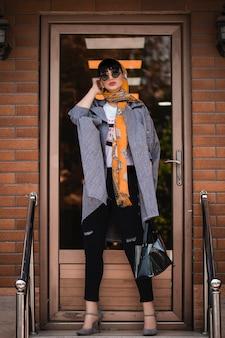 Mannequin in grijze jas en oranje sjaal