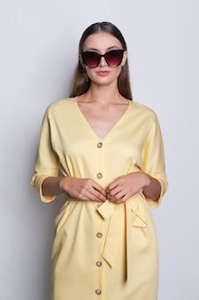 Mannequin in grote zonnebril die gele kleding met het stellen van knopen dragen