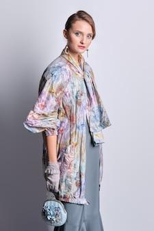 Mannequin in kleurrijke jas met pastelkleurige ritssluiting en zijden jurk