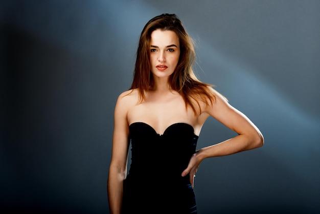 Mannequin in zwarte jurk, elegante vrouw in sexy avondjurk, mooi meisje studio geschoten op een grijze achtergrond