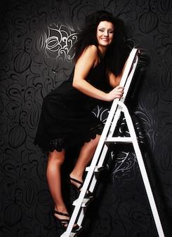 Mannequin in zwarte jurk op de ladder