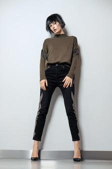 Mannequin in zwarte pruik, trui met franje en jeans met strass steentjes