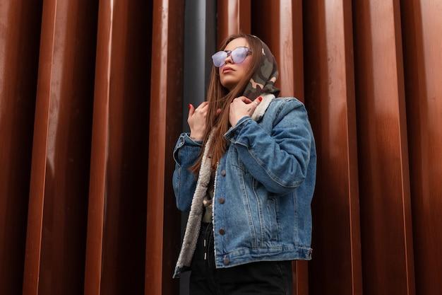 Mannequin jonge mooie vrouw in een modieuze oversized blauwe denim jasje in capuchon met paarse glamoureuze bril poseren in de buurt van rode metalen muur in de stad. hipster stedelijk meisje. amerikaanse mode.