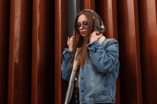 Mannequin jonge stijlvolle vrouw in blauwe jeugd spijkerjasje met paarse trendy bril rechtzetten modieuze camouflage kap en naar beneden kijken in de buurt van metalen wand buitenshuis. cool hipster meisje in de stad.