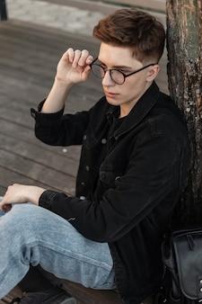 Mannequin knappe jonge man in trendy denim kleding rechtzetten vintage bril buitenshuis