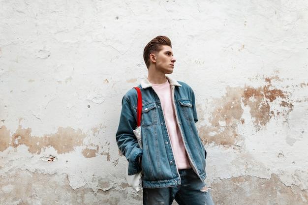 Mannequin knappe jongeman in stijlvol roze t-shirt in modieus blauw denim jasje met stoffen shopper in de buurt van vintage muur in de stad. stedelijke man in trendy kleding buitenshuis. straatstijl voor jongeren.