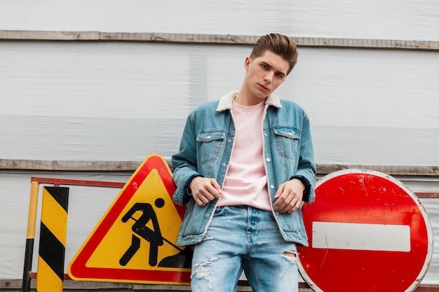 Mannequin knappe jongeman in stijlvolle blauwe denim kleding in roze vintage t-shirt geniet in de buurt van metalen verkeersborden in de stad. trendy man in casual jeanskleding. straat casual lente-zomer stijl.