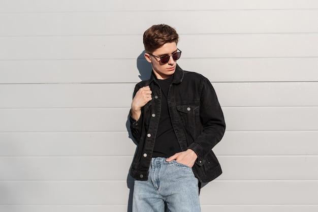 Mannequin knappe jongeman met trendy kapsel in zonnebril in zwart spijkerjasje