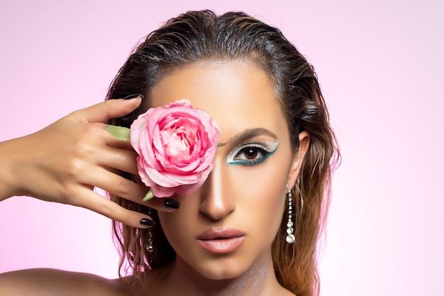 Mannequin met roze bloem op heldere muur