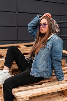 Mannequin mooie jonge vrouw hipster in jeugd violet bril in stijlvolle blauwe denim jasje in zwarte jeans in witte leren laarzen rust op houten pallets in de stad. stedelijk modern meisje buitenshuis