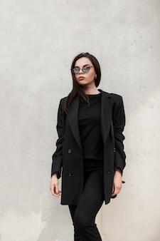 Mannequin prachtige jonge vrouw in koele spiegel zonnebril in modieuze zwarte casual jas in stijlvol t-shirt in de buurt van moderne witte muur in de stad. amerikaans sexy meisje in trendy jeugdoutfit in straat.