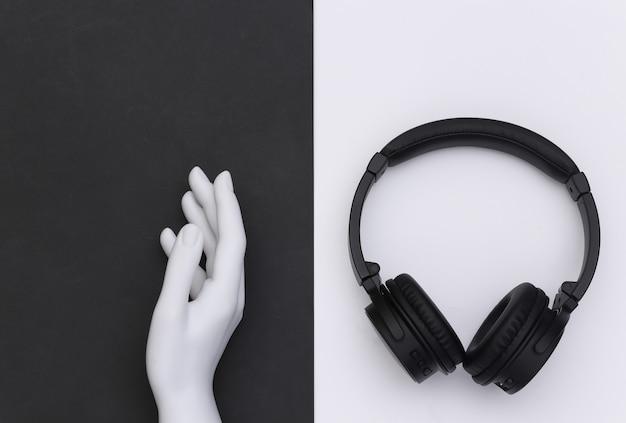 Mannequin's witte hand en stereo koptelefoon op zwart witte achtergrond. bovenaanzicht