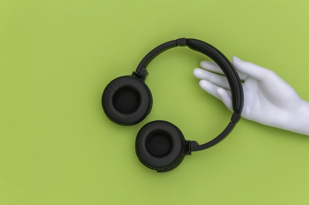 Mannequin's witte hand met stereo koptelefoon op groene achtergrond. bovenaanzicht