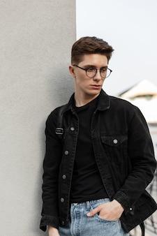 Mannequin serieuze jonge man in stijlvolle jeans jeugd vrijetijdskleding in modieuze bril met rugzak rust in de buurt van muur in de stad. trendy man buitenshuis. nieuwe collectie herenkleding. lente stijl.