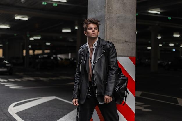 Mannequin van een jonge serieuze man in een shirt in een leren zwarte stijlvolle jas in spijkerbroek met een rugzak staat in de buurt van een pilaar op de parkeerplaats in de stad. amerikaanse trendy coole hipster-man buitenshuis.