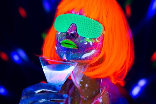 Mannequin vrouw alcoholische cocktail drinken in neonlicht, disco nachtclub. mooie danseres model meisje kleurrijke heldere fluorescerende make-up