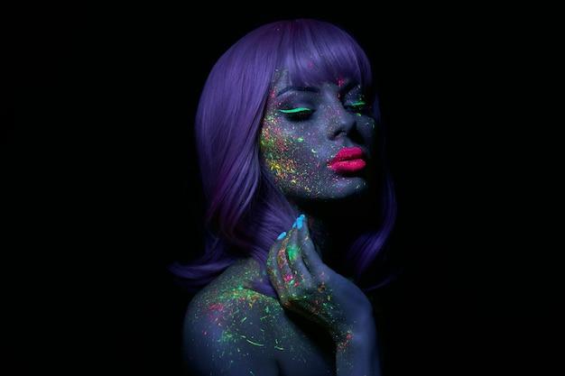 Mannequin vrouw in neonlicht heldere fluorescerende make-up, lang haar, druppel op gezicht. de mooie model roze kleurrijke samenstelling van het haarmeisje