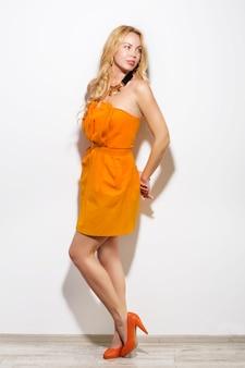Mannequinmeisje het portret van gemiddelde lengte in oranje kleding en moderne toebehoren