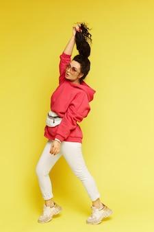 Mannequinmeisje van gemiddelde lengte in stedelijke sportkleding over gele muur. een jonge vrouw in een roze hoodie en een modieuze tennisschoen die bij de gele muur wordt geïsoleerd