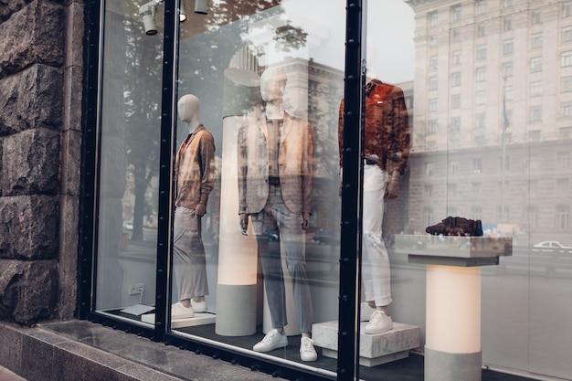 Mannequins gekleed in herfst mannelijke outfits op showcase van een winkel in het centrum. winkelen en verkoopconcept. zwarte vrijdag
