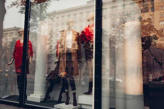 Mannequins gekleed in herfstoutfits op showcase van een winkel in het stadscentrum. winkelen en verkoopconcept. zwarte vrijdag