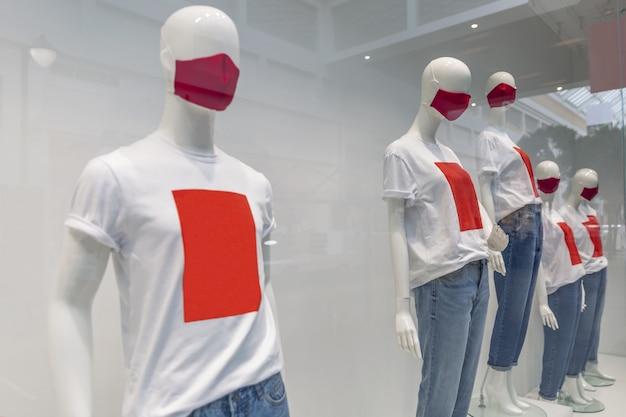 Mannequins met medische maskers en t-shirts in een etalage in een winkelcentrum. seizoensgebonden verkoop. coronapandemie.