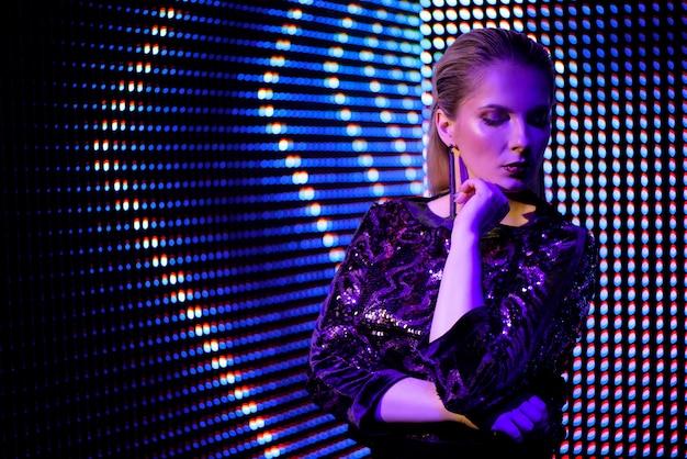 Mannequinvrouw in kleurrijke heldere neon uv blauwe en purpere lichten, mooi meisje