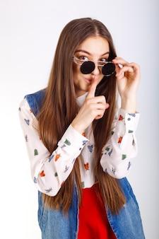 Mannequinvrouw in zonnebril, het rode minirok stellen op wit