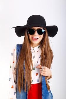 Mannequinvrouw in zwarte hoed, zonnebril, het rode minirok stellen op wit