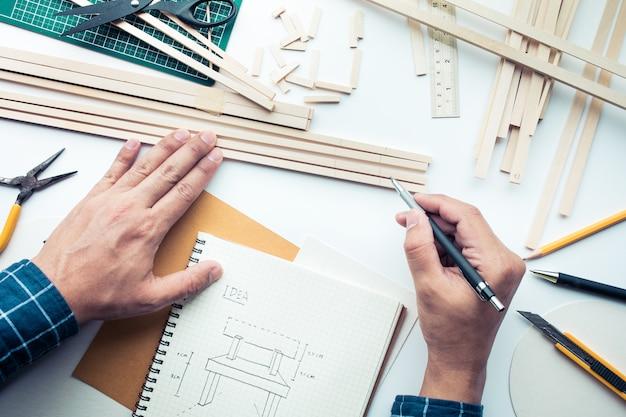 Mannetje bezig met werktafel met balsahout materiaal