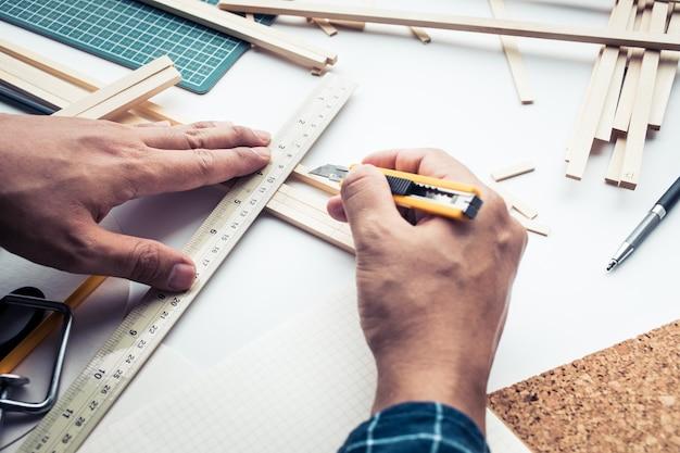 Mannetje bezig met werktafel met balsahout materiaal.